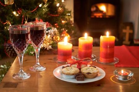 Een kerstboom scène 's nachts met glazen wijn, mince pies, aangestoken kaarsen en vuur. Stockfoto