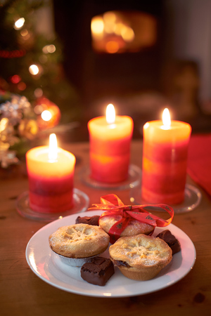 A Christmas tree scene at night with mince pies, lit candles and fire. photo