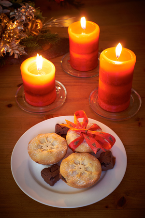 A Christmas tree scene at night with mince pies and lit candles photo