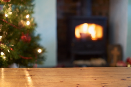 A Christmas tree scene background with a lit fire and in focus table.
