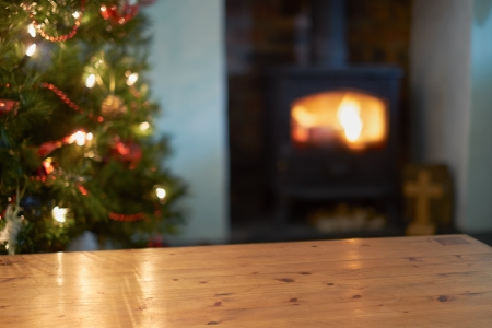 hearth and home: A Christmas tree scene background with a lit fire and in focus table.