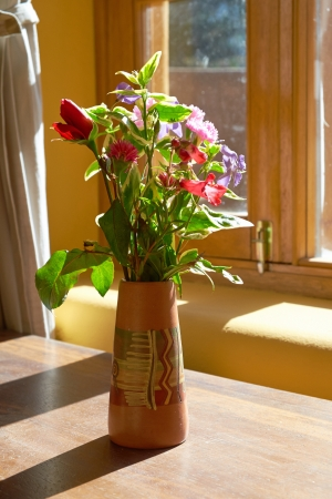 Flowers In a vase on a sunny window sill. photo