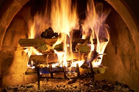 log fire: Una stufa a legna brucia furiosamente in un camino in pietra. Archivio Fotografico
