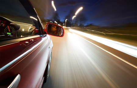 A man driving a car at night on a straight road.  photo