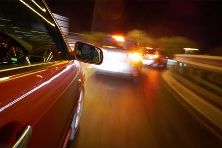 Een man het besturen van een auto 's nachts op een rechte weg