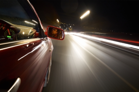 A man driving a car at night on a straight road