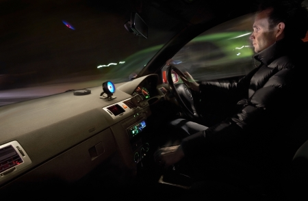 An interior view of a man racing a car at night. photo