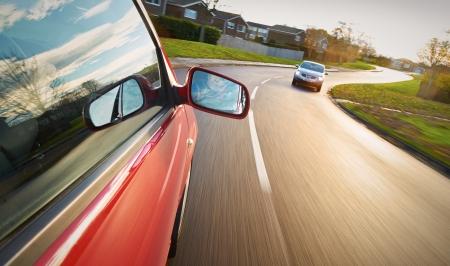 aandrijvingen: Een man rijden een rode auto in de richting van een bocht in de weg.