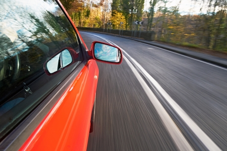 cornering: A man driving a red car towards a bend on a country road. Stock Photo