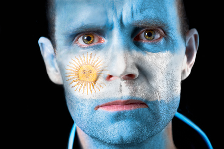 An intense stare from a football fan with their face painted with the Argentine flag  photo
