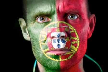 malandros: Una intensa mirada de un aficionado al f�tbol con su cara pintada con la bandera portuguesa