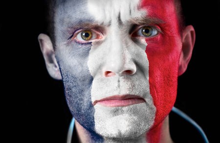 An intense stare from a football fan with their face painted with the French flag. photo