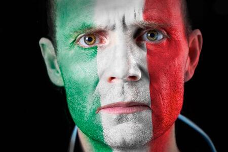 malandros: Una intensa mirada de un aficionado al f�tbol con su cara pintada con la bandera italiana Foto de archivo