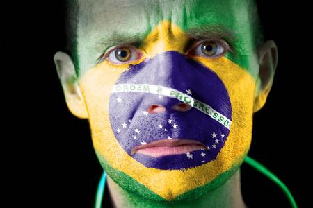 malandros: Aficionado al f�tbol agresivo con su cara pintada con la bandera de Brasil Foto de archivo