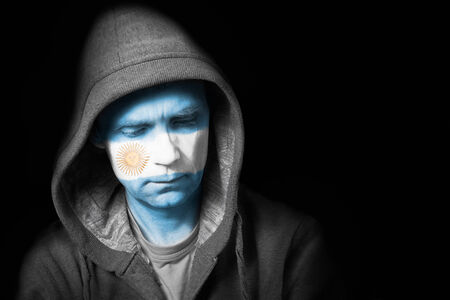 argentinian flag: A sad expression on the face of a football fan with their face painted with the Argentinian flag  Stock Photo