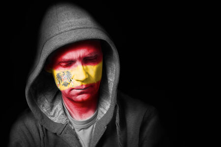 A sad expression on the face of a football fan with their face painted with the Spanish flag  photo