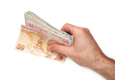 A hand holding a mixture of Turkish Lira Currency, on a white background  photo