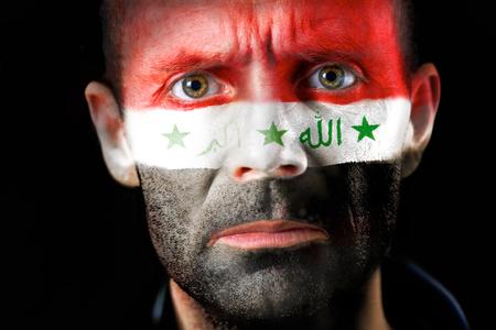 malandros: Una intensa mirada de un hombre con la cara pintada con la bandera de Irak.