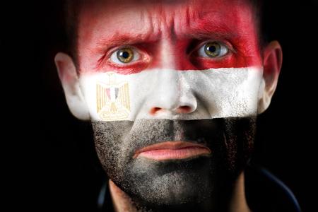 malandros: Una intensa mirada de un hombre con la cara pintada con la bandera egipcia. Foto de archivo