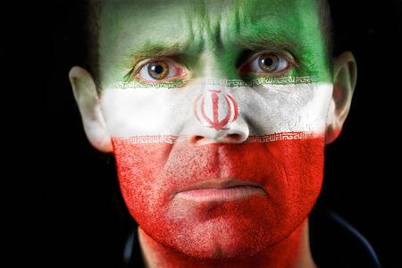 malandros: Una intensa mirada de un hombre con la cara pintada con la bandera iran�.