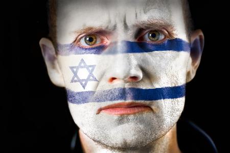 malandros: Una intensa mirada de un hombre con la cara pintada con la bandera de Israel.