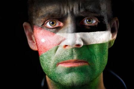 malandros: Una intensa mirada de un hombre con la cara pintada con la bandera de Jordania. Foto de archivo