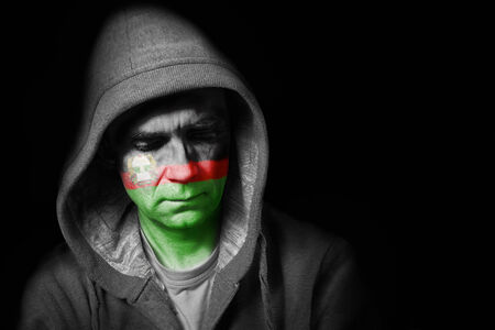 afghan flag: A sad expression on the face of a man with their face painted with the Afghan flag