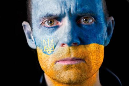 malandros: Una intensa mirada de un hombre con la cara pintada con la bandera de Ucrania