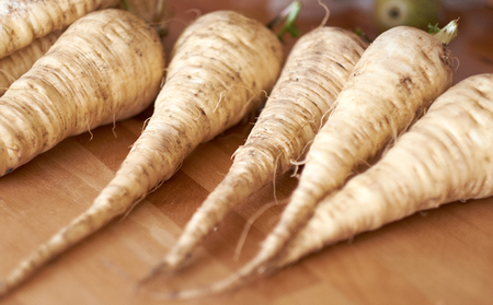 Fresh home grown parsnips lying on a wooden bench in a kitchen