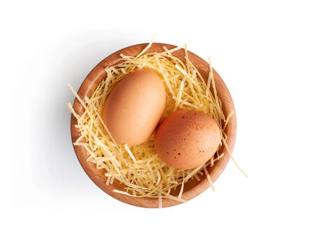 Two fresh hens eggs on some straw in a wooden bowl on a white background. photo
