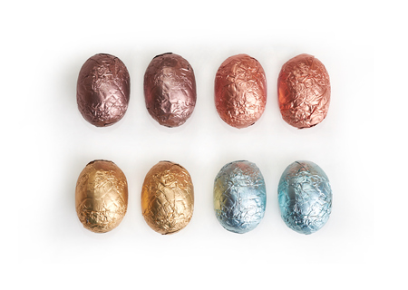 A Selection of chocolate Easter Eggs wrapped in coloured tin foil on a white background  photo