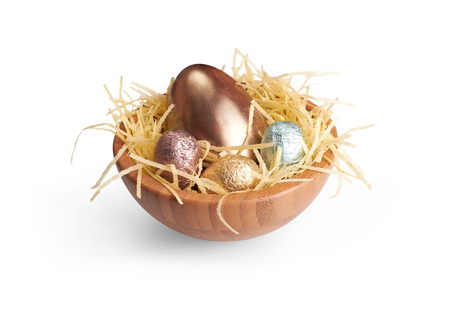 A wooden bowl of chocolate Easter Eggs wrapped in coloured tin foil on a white background  photo