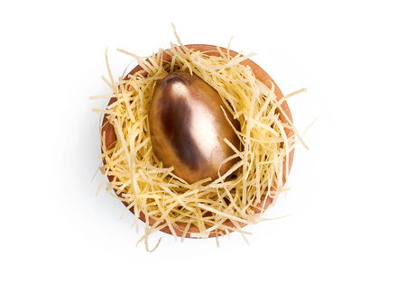 A wooden bowl with a golden chocolate Easter Egg on a white background. photo