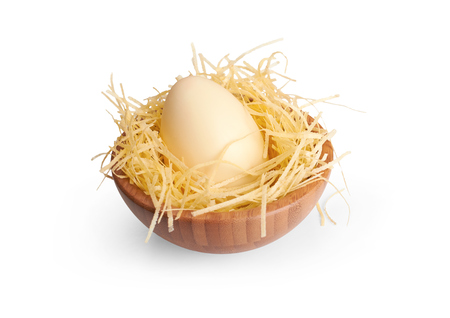 A wooden bowl with a white chocolate Easter Egg on a white background. photo
