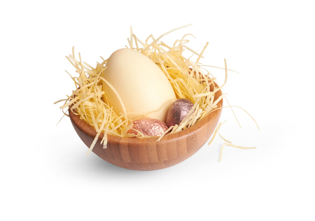 A wooden bowl of chocolate Easter Eggs on a white background. photo