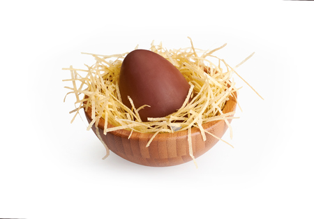 A wooden bowl with a large chocolate Easter Eggs on a white background. photo