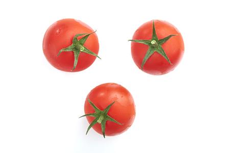 tomate cherry: Tomates rojos aislados en un fondo blanco.