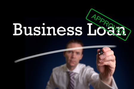 An underwriter writing Business Loan approved on a screen. photo