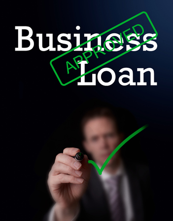 underwriter: An underwriter writing Business Loan approved on a screen.