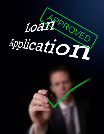 underwriter: An underwriter writing Loan Application approved on a screen.