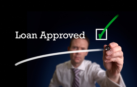 personal banking: An underwriter writing Loan Application approved on a screen.