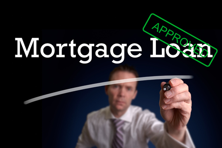 personal banking: An underwriter writing Mortgage Loan approved on a screen.