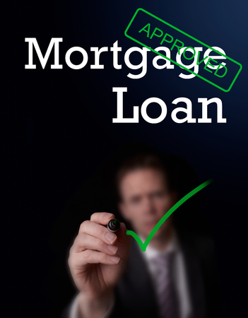 underwriter: An underwriter writing Mortgage Loan approved on a screen.