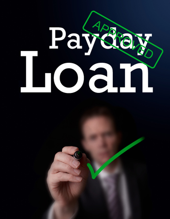 underwriter: An underwriter writing Payday Loan approved on a screen. Stock Photo