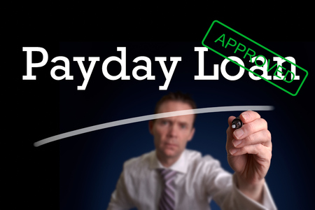 authorize: An underwriter writing Payday Loan approved on a screen. Stock Photo