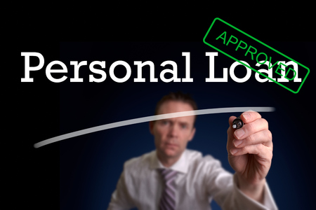 An underwriter writing Personal Loan approved on a screen. Stockfoto