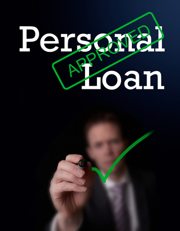 personal banking: An underwriter writing Personal Loan approved on a screen. Stock Photo