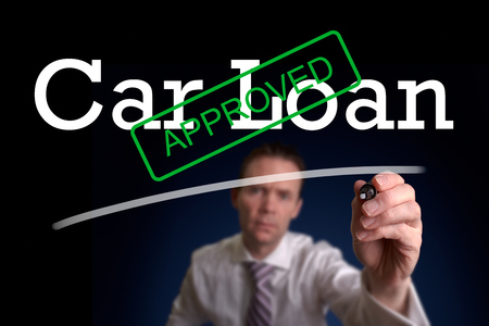 underwriter: An underwriter writing Car Loan approved on a screen.