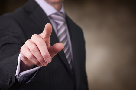 finger pointing: A business man pointing his finger at you.