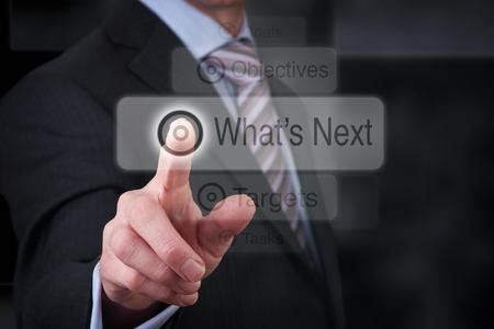 Business goals concept, mans hand pressing a Whats Next Button.